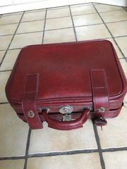 roter Koffer und Giesskanne